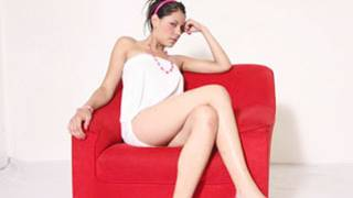 This stunning brunette sitting in a red chair and she seems ready to fuck